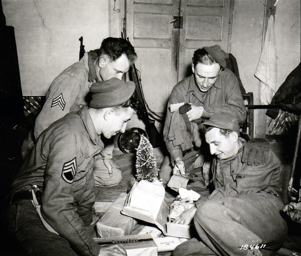Sitting around a miniature Christmas tree and opening a Christmas package are (front row, left to right) S/Sgt. John F. Suchanek; and Pfc. Joseph G. Pierro; and (back row) Sgt. Charles M. Myrich; and Sgt. Leon L. Oben. All are members of F. A. Bn., 3rd Div. Pietramelara, Italy. December 16, 1943
